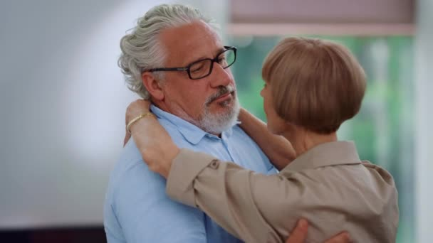 Starší muž a žena tančí v páru doma. Pár se na sebe dívá