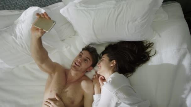 Paar schaut sich im Haus um. Sexy guy mädchen liegend bett im luxus hotelzimmer.