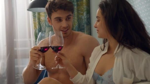 Sexy Paar trinkt Rotwein im Bett. Unbekleidete Liebende reden im Hotelzimmer.