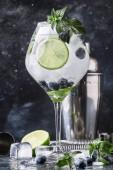Fotografie Letní alkoholické borůvkový koktejl mojito s rum, máta, limetky a ledu, panel nástrojů, šedé pozadí, Selektivní ostření