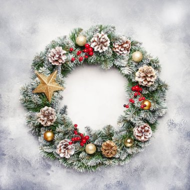 Christmas or New Year frame flat composition with green snow fir branches, pine cones, golden snowflakes, Christmas balls, red berries on white gray background, top view