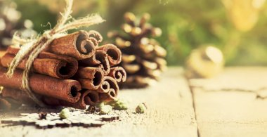 New Year or Christmas composition with spices for making hot winter drink, cinnamon, cardamom, cloves and anise, vintage wooden background, selective focus