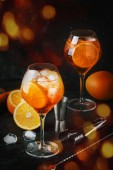 Aperol spritz cocktail in großen Weinglas, Sommer italienische niedrigem Alkoholgehalt Kaltgetränk, dunkle bar Theke Hintergrund mit Werkzeugen, Sommer Stimmung Konzept, selektiven Fokus vertikales Bild