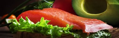 Selection of healthy foods and fats: salmon, avocado, tomatoes, lettuce, olive oil, onions and herbs, old wooden kitchen table background, banner, selective focus