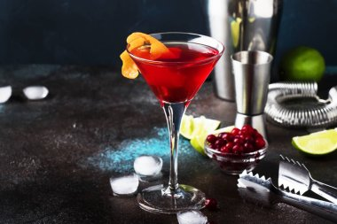 Classic alcoholic cocktail cosmopolitan with vodka, liqueur, cranberry juice, lime, ice and orange zest, dark bar counter background, night mood, space for text