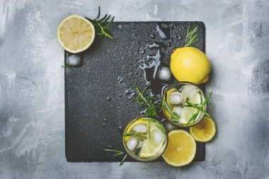 Summer fizzy cocktail with lemon, rosemary and ice, gray table background, toned image, top view