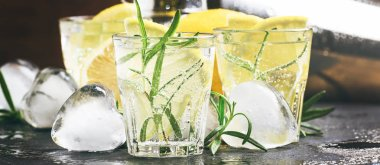 Refreshing cool summer lemon drink with rosemary, ice and gin tonic, black stone bar counter background, copy space, banner, selective focus