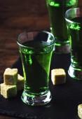 Fotografie Absinth - starkes alkoholisches Getränk, grüne Wermuttinktur in Gläsern auf dem alten Holztisch, Platz für Text