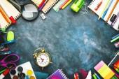 Zpět na školní pozadí s prostorem pro text, poznámkové bloky, pera, tužky, další papírnické papíry na stolní desce s modrou křídou, koncept vzdělání, plochý, horní pohled