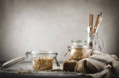 Uncooked green buckwheat groat in glass jar, healthy vegetarian food on gray kitchen table, copy space, selective focus