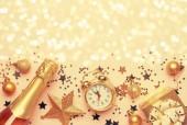 Karácsony vagy újév összetétele, a keret, a rózsaszín háttér, arany karácsonyi díszek, csillagok, hópelyhek, labdák, ébresztőórával, díszdobozban és üveg pezsgő, top view