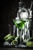 grüner alkoholischer Cocktailmönch mit trockenem Gin, Wermut, Likör, Limettenschale und Eis, Barwerkzeugen, dunklem Hintergrund