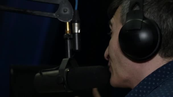 Photo A radio station, a male DJ speaking into a microphone.
