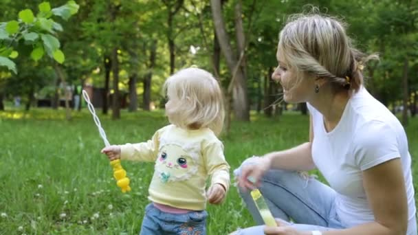 Woman and child playing with soap bubbles in nature.