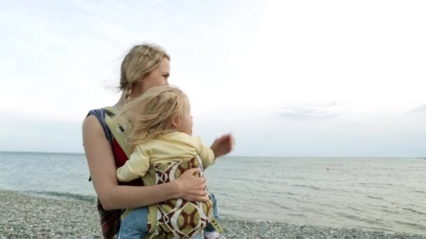 Woman with baby on the background of the sea.