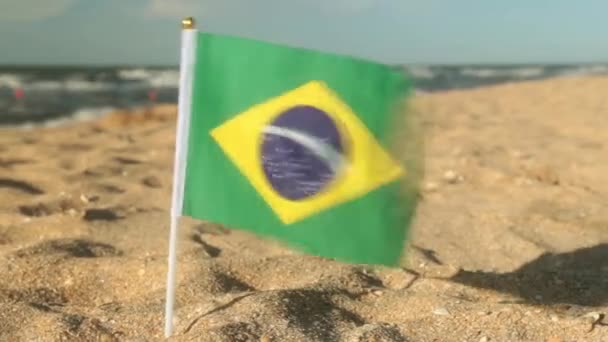 Flag of Brazil on a sandy beach.