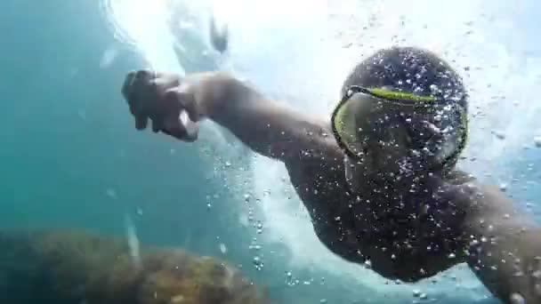 Ein Mann mit Maske zum Schnorcheln segelt zum Meer.