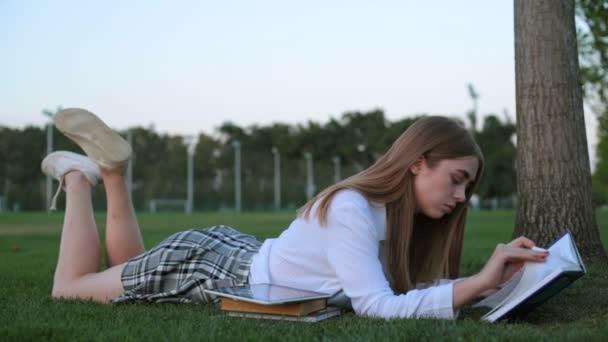 Student v parku, čtení knihy. Mladá žena s knihou.