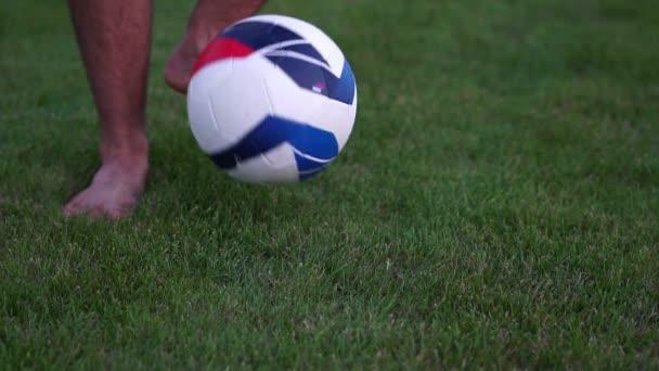 Fotbalový míč a zelené trávy. Muž s fotbalovým míčem, pomalý pohyb