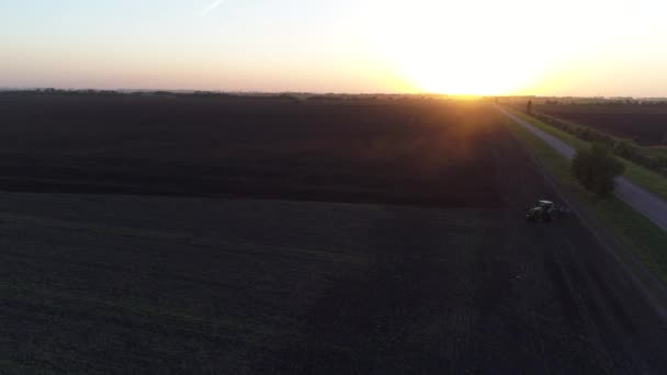 Sunset or sunrise, field and tractor. Farmer, agriculture.