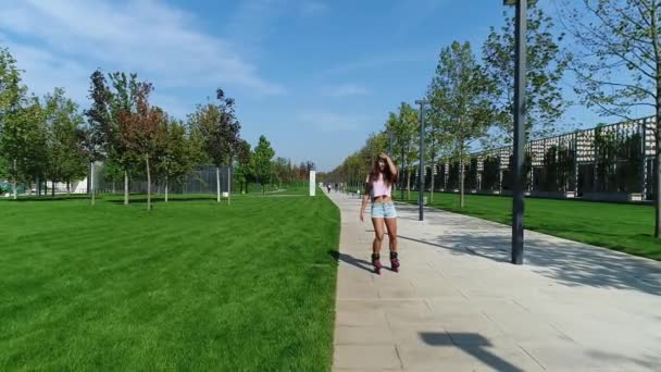 Mladá sexy žena na kolečkové brusle v parku, pomalý pohyb