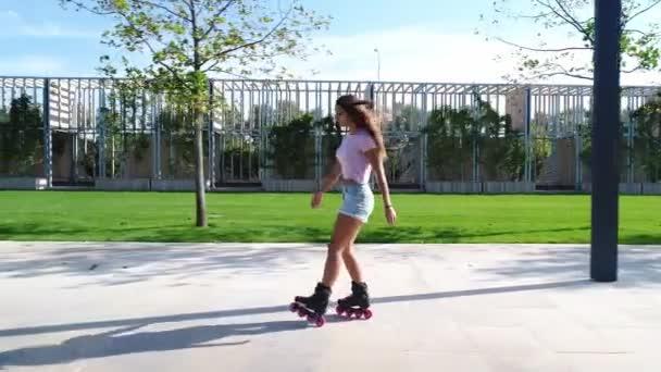 Sexy žena na kolečkových bruslích v parku. Sportovní holka jezdí na kolečkových bruslích