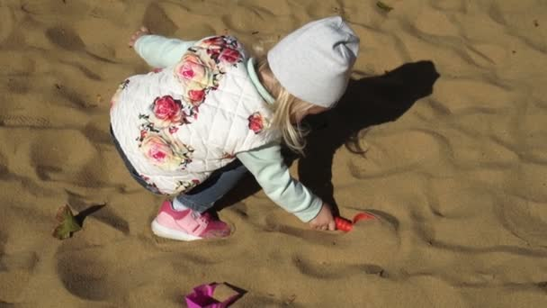 The child plays in the sandbox.