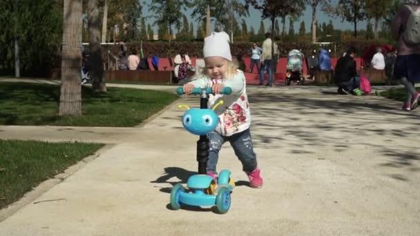 dítě jezdí dětský skútr. Dívka jezdí na skútru v parku