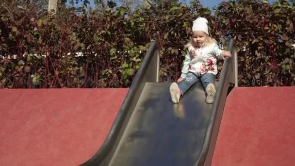 Cheerful child riding with a childrens slide on the playground.