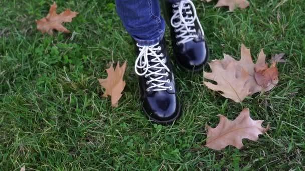 Podzim, žena chodí přes listy. Dámské boty detail