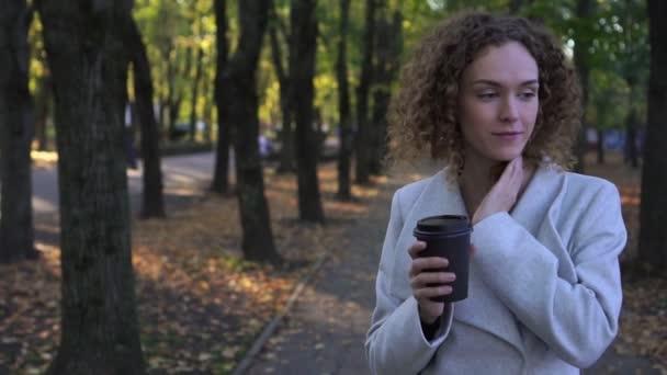 Gyönyörű fiatal nő italok kávé papírpohár az őszi parkban.