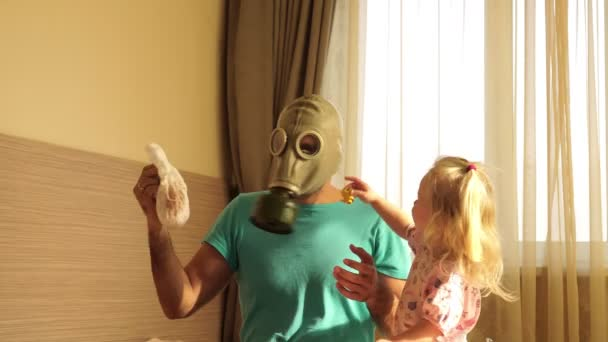 A man in a gas mask with disgust changes a dirty baby diaper. Father and child.