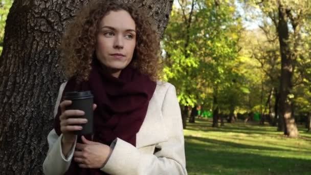 Beautiful young woman is freezing and drinking coffee in the park.