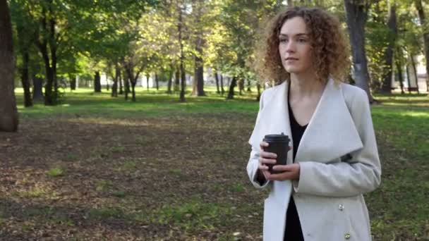Autumn, business woman drinks coffee in the autumn park.