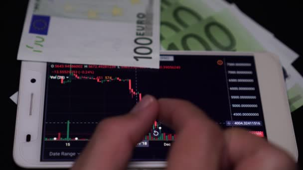 Férfi befektetői tanulmányok a mutatók az állomány vagy valuta csere egy okostelefon.