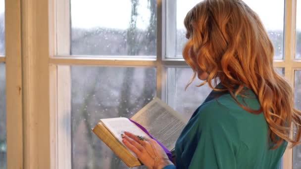Őszén, egy gyönyörű fiatal nő az ablak mellett olvasott.