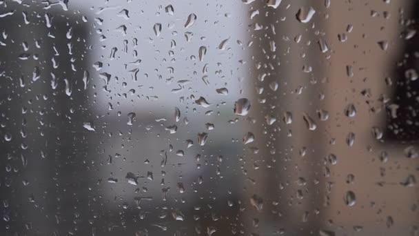 Kapky deště stékají dolů na sklo.
