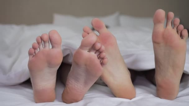 Mladý pár v lásce na posteli, nohy pod kryty detail.