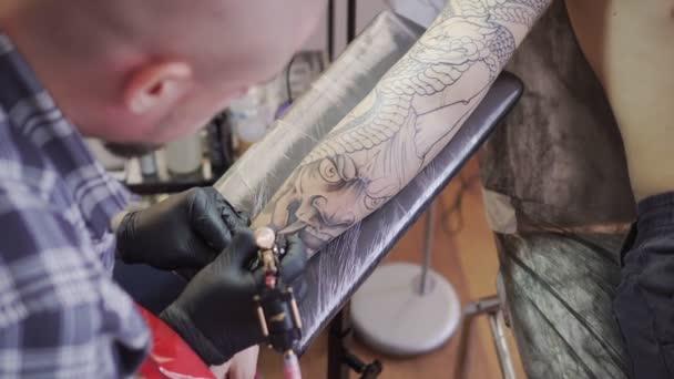 Muž tattoo umělec. Tetování, tetovací salon