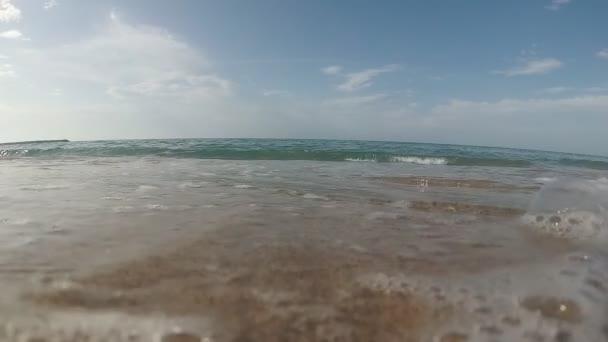 Lassú mozgás: tengeri hullám fröccsenés a homokos parton, víz alatti videó.