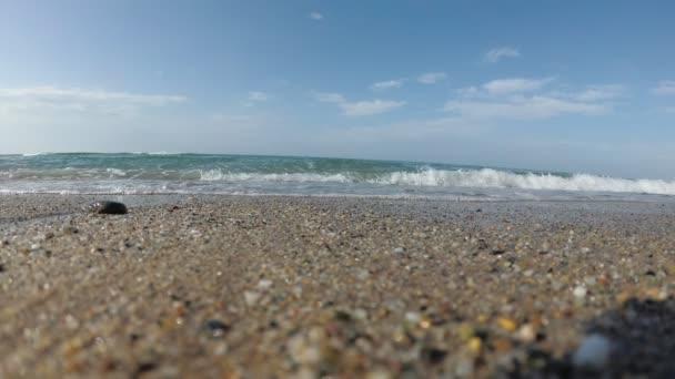 Homokos tengerpart, a tengerpart emberek nélkül. Tengeri hullám gördült be a partra, lassított.