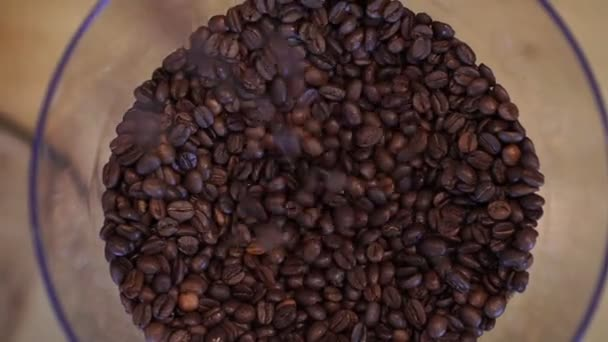 Roasted coffee beans close-up. Coffee beans are poured into a coffee grinder.