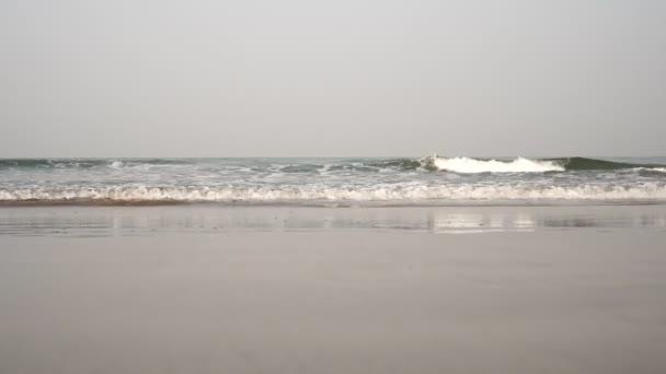Sandstrand und Meereswellen. Meeresgrund, Küste ohne Menschen, blauer Himmel