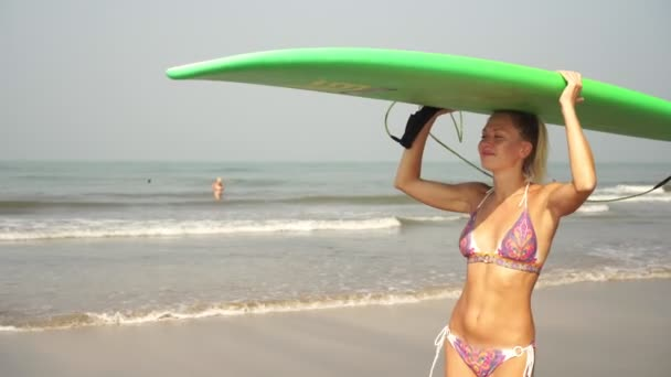 Portrait of a young attractive woman with a surfboard over ocean background