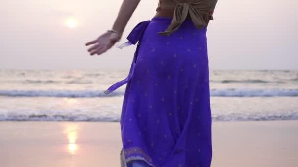 Eine junge Frau in orientalischer Kleidung tanzt am Strand