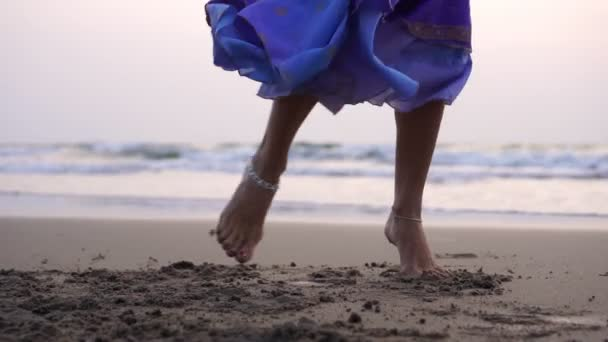 Eine junge Frau tanzt an einem Sandstrand vor dem Hintergrund des Meeres