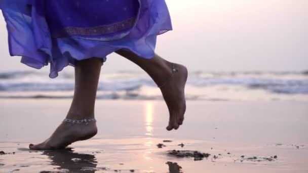 Schöne Mädchen tanzen auf dem Sand vor dem Hintergrund des Meeres