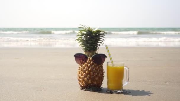 Turista ananász napszemüvegben pihen a tengerparton