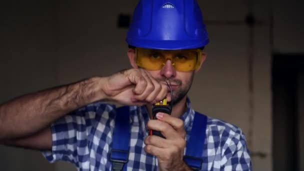 Portrait of a male builder. Worker or builder measures with a construction tape