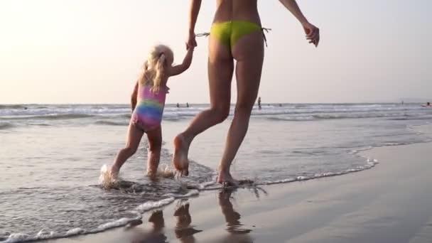 Máma s dítětem běží podél vln na písečné pláži, zpomalený film